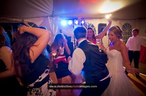Bride and Friends Dancing under tentedwaterfront wedding